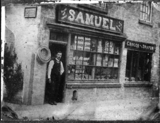 William Samuel standing in the shop entrance on Market Street in the early 1900s from a glass photographic plate, measuring 3.25 x 4.25 inches. The signs on the end wall indicate that the premises were licensed to sell cigarettes and tobacco. The sign over the shop also advertises 'boots and shoes' and 'suits to measure'