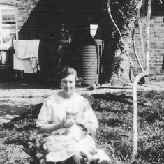 Winnie Bray in the back garden of the Bray's house in Muston with one of the family's pet cats, c. 1920.