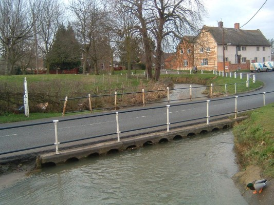 The next bridge is a low level one near the west end of the church, which carries the road to Newark. This floods on a regular basis due to the fact that it carries a number of small tunnels, which often get blocked with twigs and leaves floating down the river. Early photographs show the ford before this structure was built. Today, it keeps the roadway clear of the water most of the time, though it can become flooded during periods of heavy rain - cars then pass through carefully, some don't make it and have to pushed or towed out.