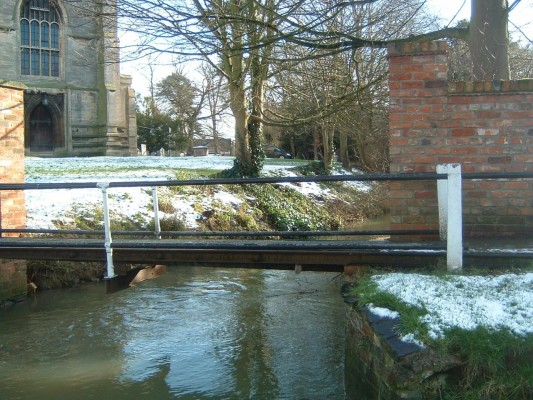 Alongside this is a wooden footbridge. The river then winds around the church perimeter. Some 70 yards upstream there used to be a footbridge connecting The Rectory grounds with the church but this was removed when The Rectory was sold for development on the 1980s.