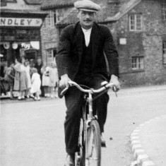 Mr. Slater cycling past Standley's shop.