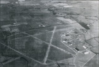 Bottesford from the air, looking north west, 1990. Although part of the main runway and the dispersals have long since gone, their 'ghosts' are still visible, as are the hangars and the classic 'A' shape of a wartime bomber airfield