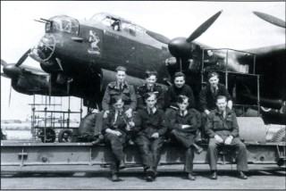 F /Sgt Des Sullivan RAAF and members of his air and ground crew sit on a bomb trolley in front of 'their' ED764 'N-Nancy' - or 'Nuts to the Nazis' as the Olive Oyl nose art proclaims. 'Nancy' was shot down over Peenemunde whilst being 'borrowed' by Frank Dixon and crew