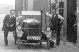 Picture showing garage staff and customer with an open topped car, 1920s at Christmas and Chorlton's Garage, High St., Bottesford
