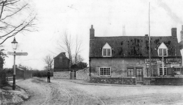 Bottesford, corner of High Street and Belvoir Lane, c.1910, showing the old shop on the corner, a man standing in the road, and the old finger sign-post.   Collection of Mrs Yolande Honey