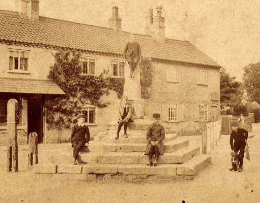 Late Victorian children sitting on the steps of the Market Cross, Bottesford: a faded sepia print enhanced digitally | Contributed by Mr Mike Saunders