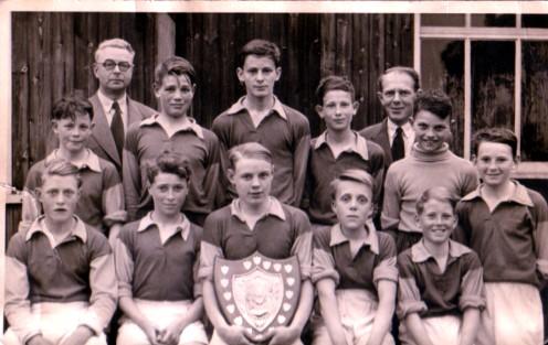 Mr Dewey, headmaster, with the school football team showing off the shield they had won. | Brian Braithwaite