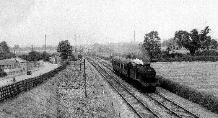 Steam train at Orston Lane level crossing: showing a steam train heading south across Orston Lane level crossing, with the former army camp on the right (west of the NS track).   From the collection of the late Mr Ken Greasley