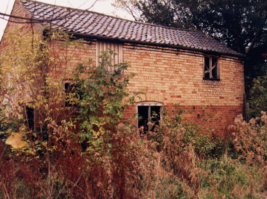 A picture of the barn which stood on Church Street and belonged to the Old Rectory in Bottesford prior to redevelopment of the rectory c.1980. The picture shows a brick and pantile building in an overgrown yard. | Contributed by Mrs Viv Finch