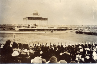 Crowds watching the Durbar ceremony in which the King and Queen are seated beneath the ceremonial canopy. | From the Swallow family collection of Mrs Viv Finch