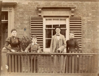 This picture was taken outside Joseph Hudson's home at 28 Queen Street, adjacent to the saddlery workshop (no longer standing) on Queen Street in Bottesford, c.1894. It shows the three Hudson children with their mother: from left to right, Herbert's sister Beatrice, Herbert Wright Hudson himself, his elder brother Frederick, and their mother Mary Hudson. | From the Hudson family archive, courtesy of Mr Jonathan Hudson.