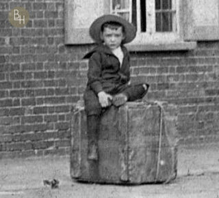 Arthur Geeson sittng on a wooden crate in front of the family grocer's shop in Church Street, Bottesford, in 1903. | Bottesford Heritage Archive: from the collection of Mrs Mary Owen.