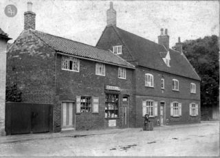 Geeson's grocery shop, Church Street - a general view in which Arthur Geeson is seen sitting on a crate in front of the shop in 1903. | Bottesford Heritage Archive: from the collection of Mrs Mary Owen.