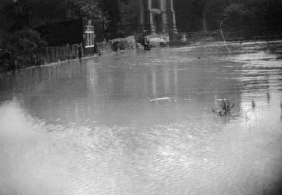 Rectory Lane ford, heavily flooded, Greaves' bicycle shop on the left.