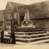 Postcard of the Market Cross and Stocks, with the village school behind.