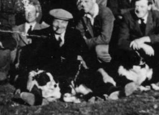 Arthur with sheep dogs sitting in the sun on the grass by the Red Lion with a group of local men waiting for the coach to arrive for a day's outing. | Courtesy of Mrs Barbara Sutton