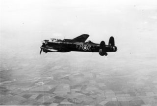 A Lancaster bomber in the air. | Bottesford Archive