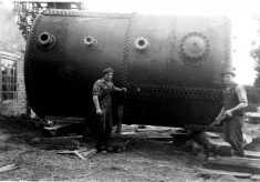 Men standing by a large cylindrical boiler.