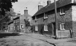 Church St in the 1950s, before demolition of the end row of cottages. The house on the right is the former Six Bells ale house.