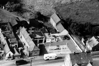 An aerial picture of shops, garage and the houses on the High Street, opposite the Rutland Arms, 1965. The row of terraced cottages behind the shops was known as Standley's Row.