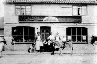 J.D. Robinson & Co, circa 1900. The children are (L to R): James, W. (b.1893, d.1934); Annie (b.1891); Victoria M (b.1897) on the knee of Mrs Caroline Robinson (b. 1856); George (b.1889, d.1941) holding the donkey; Richard (b. 1895, d.1918 'in the Great War') - sitting on the donkey.                                                                                                                      | Bottesford Local History Archive