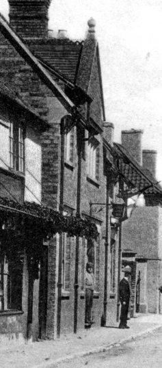 Detail from the picture of Market Street around 1900, showing the coffee shop, a man standing in the doorway and the shop's lamp over the door. | Bottesford Local History Archive
