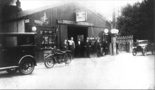 Christmas and Chorlton's garage in the 1930s, showing the bicycle shop alongside the repair shop and fuel pumps.          | Bottesford Local History Archive