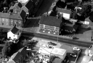 1980s aerial view of Nicholl's Garage and the Rutland Arms. | Bottesford Local History Archive