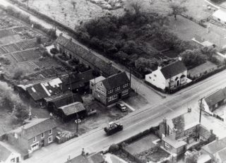 1950s aerial photograph of the High Street and Barkestone Lane/Albert Street junction. On the far (south) side can be seen (L to R) Eric George's shop, the old Post Office, W.J. Robert's premises and 'The Rosary'. On the northern side of the High Street, in the foreground: Vine House and the single-storey Gas Showroom. | Bottesford Local History Archive