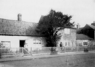 Norris family houses in the early 1900s – Nos. 16 and 18 High St. Mr Ian Norris has assisted in identifying the people in this photograph, who are Frank and Elizabeth Norris. They had twin sons Frank & John. Elizabeth is holding Frank and Frank is holding John. The single-storey house to the left in the picture was built of mud. It was demolished in the 1960s and a new house was built - No 18. The brick built cottages to the right in the picture were converted into one dwelling - No 16. | Bottesford Local History Archive
