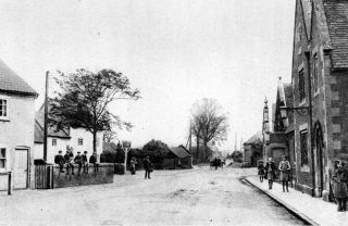 A photograph looking eastwards along Grantham Road, Bottesford, with the village school on the right, and the Red Lion behind the tree on the left. The blacksmith's shop and the schoolhouse can be seen in the background.   | Bottesford Local History Archive