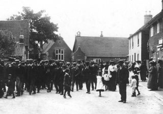 Bottesford Friendly Society marching to church, c.1911. The village school building is seen in the background, including the original ornate brickwork of the entrance hall to the infants classroom (nowadays called the Fuller Room). | Bottesford Local History Archive