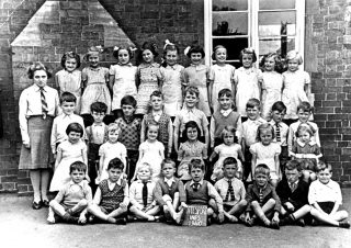 Bottesford infants in 1940.  Back row (left to right): Teacher Miss Morris (Mrs Edinburgh), not identified, Sheila Coy, Pat Robinson, Ann Lovett, Paddy Jameson, Vera Skinner, Jean Bend, Daphne Marsden, Eileen Fenton, Kathleen Doubleday. Third row (left to right): Francis Stubley, Herbert Turner, John Skinner, Richard Pacey, Keith Samuel, Brian Branston, Jeff Boland, George Pearson, Ian Norris. Second row (left to right): Pat Taylor, Beryl Lamb, Dot Bend, Margaret Deacon, Sheila Mumby, Gina Topps, Gillian Isaac. Front row (left to right): Maurice Fisher, Gerald Pacey, Peter Holmes, Richard Higdon, Peter Stanley, Gel Dolby, Peter Abbott, not identified, Peter Olley. | Bottesford Local History Archive