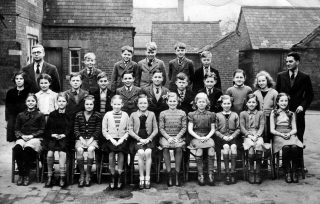 A Bottesford school photo taken in the school yard, about 1950. Back row L-R: Mr. Laurie Dewey, Des Rayson, David Bend, Michael Taylor, George Norris, Conrad Taylor; Middle Row: ... Dammes, Pat Barnes, John Simpson, Neville Bagnall, Geoff Rayson,  ...  , Norman Gail,  ...  , Jean Bolland, Pat Lightfoot, Mr. Davies; Front row: Margaret Fisher, Irene Young, Ann Ducker, Ann Jallands, Anne Dunsmore, Joy Baggaley, Angela Bradshaw,  ...  , Sylvia Guy,  ...  . | Bottesford Local History Archive