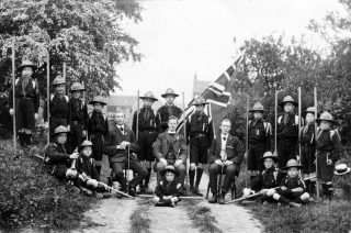 Bottesford Scout Troop, ca.1912: Canon Vincent-Jackson seated in centre, Charles Calcraft standing behind him, Bill Sutton Snr seated on grass with bugle. | Bottesford Local History Archive