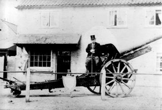 The captured German artillery piece, on display by the Cross and Taylor's butchers shop, Bottesford, with butcher Mr Arthur Edward Taylor seated on it. | Bottesford Local History Archive