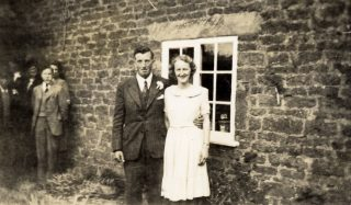Les and Ruby Calcraft at their wedding, by the farmhouse in 1948. | Bottesford Local History Archive