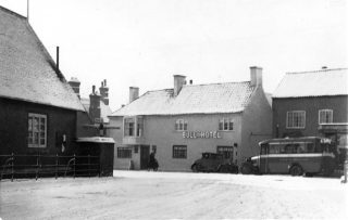 A car and Randell's coach outside the Bull. | Bottesford Local History Archive