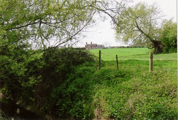 Across the River Devon, the land rises to the cottage on the horizon.