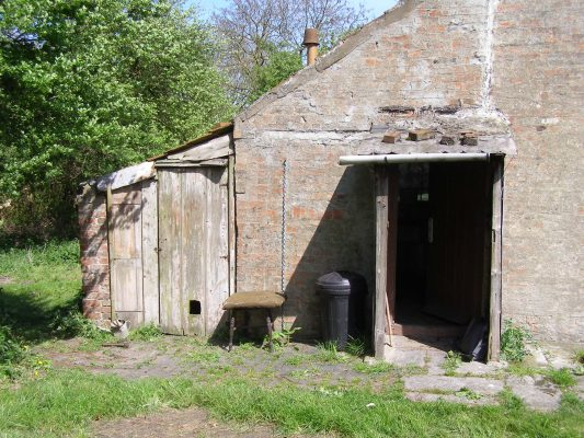 The lean-to kitchen, its porch roof weighed down with bricks, and the second lean-to where the copper was located.   Neil Fortey
