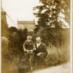 In this picture, a man and boy pose by the side of Belvoir Road just north of the mill by the Grantham Canal. In the background are the mill wheel and house. The boy may be the younger son, Frank Marston.   Janet Dammes