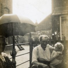 This family scene appears to be at the rear of the Marston's home on Queen Street. To left is probably the end of the Queen St mill buildings, and in the background is Queen Street and part of Tappins' cottage. Thw people are probably Frank Marston holding infant Daphne, and an unidentified woman holding an umbrella at the left edge of the picture.   Janet Dammes