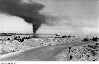 """Image from the German Federal Archives shows: """"The road from Bardia to Tobruk on 21 June 1942 with British prisoners of war on the left, sunken ships in the harbour and smoke over the port."""" 